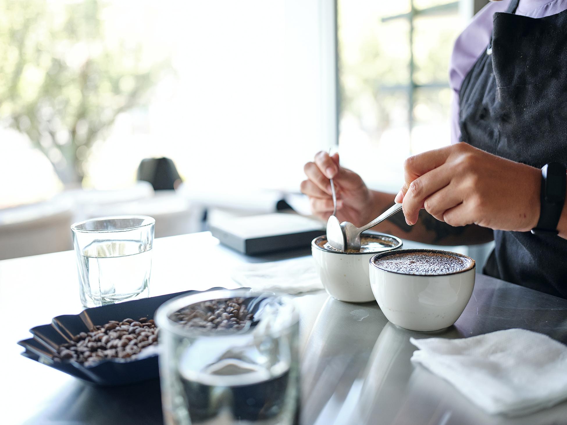 Nahaufnahme der Hände mit zwei Löffeln beim Schröpfen von Kaffee