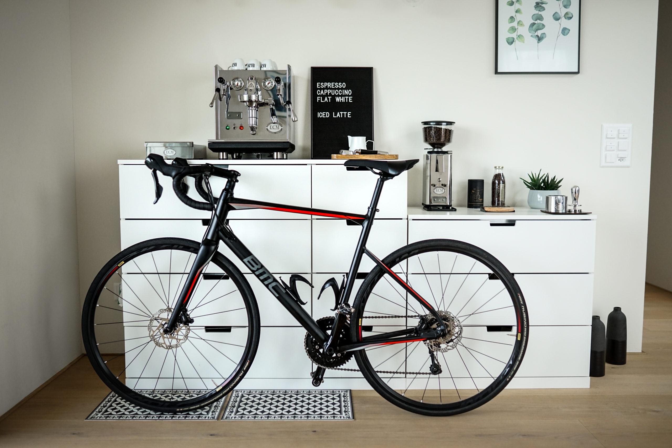 Rennvelo das vor einer Kaffeemaschine steht