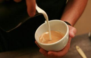 Barista der ein Cappuccino macht