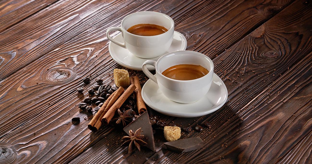 Zwei Tassen frisch gebrühter Espressokaffee mit Kaffeebohnen auf einem rustikalen Holztisch
